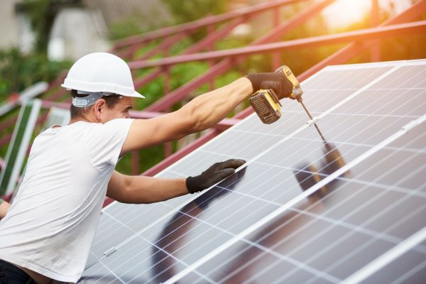 Professional technician working with screwdriver connecting blue shiny solar photo voltaic panel to metal platform on warm sunny summer day. Stand-alone exterior solar panel system installation.
